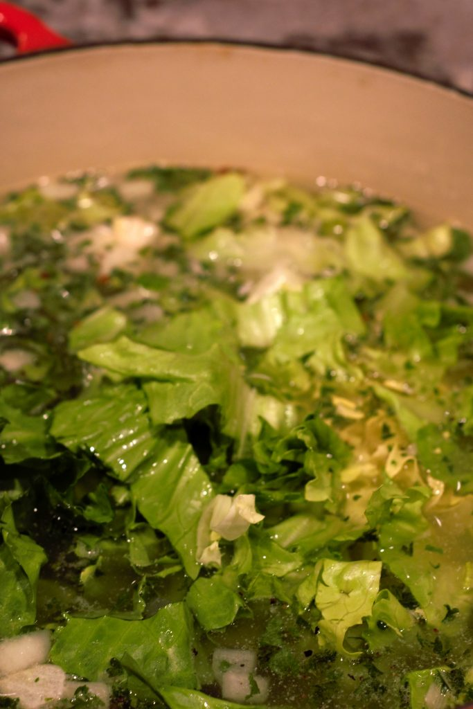 16 Cups of water are added and brought to a simmer. Cleaned and chopped escarole are added.