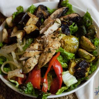 Bowl of bright and beautiful roasted vegetables with well browned chicken breast meat over red lettuce.