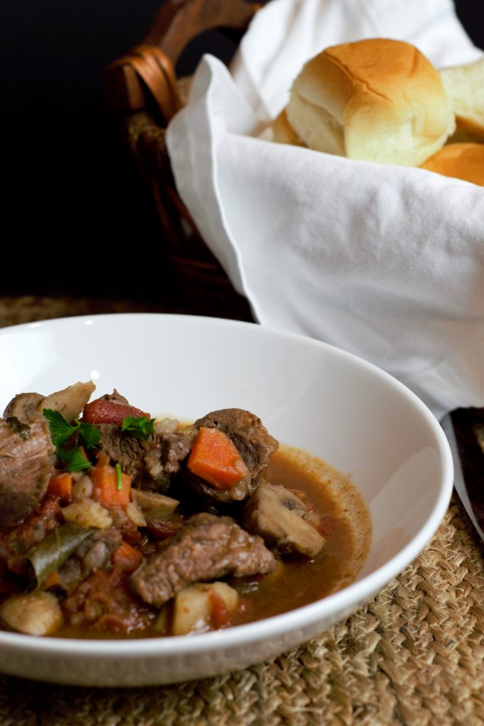 A beautiful bowl of Instant Pot Beef Stew in a rich gravy served with fluffy rolls.