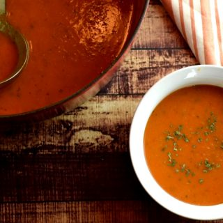 White bowl with tomato basil bisque soup.