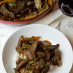 plated pepper steak and glass of red wine